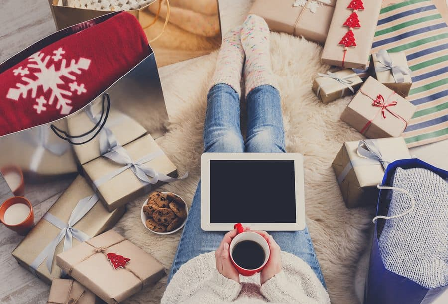 Image of woman sitting on the floor with a tablet. She is surrounded by wrapped boxes and gift bags