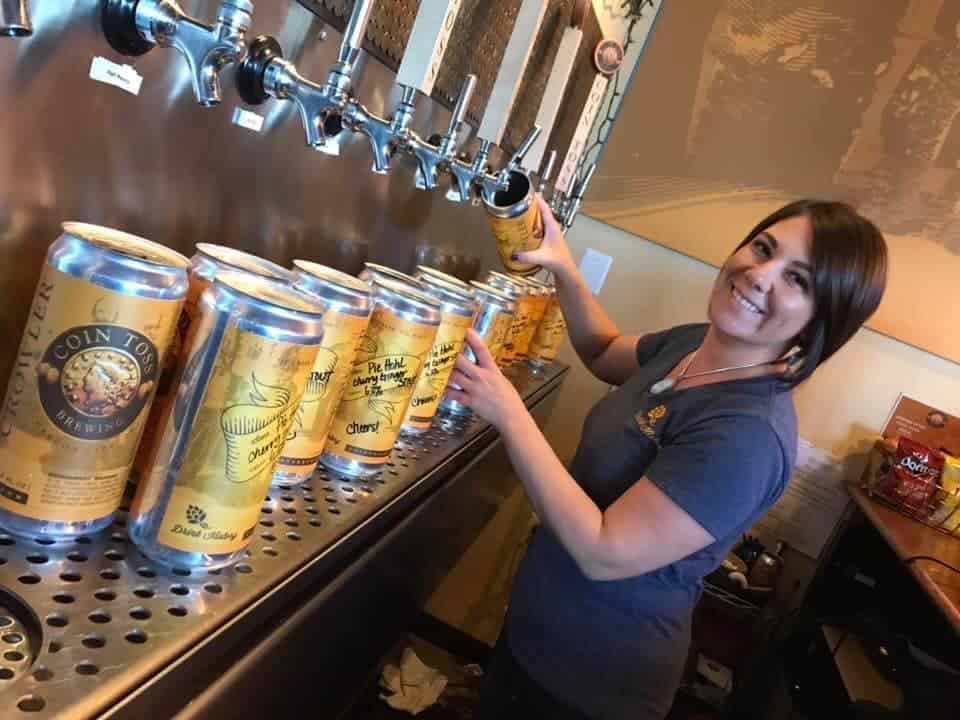 A server fills aluminum containers with beer for pickup and delivery
